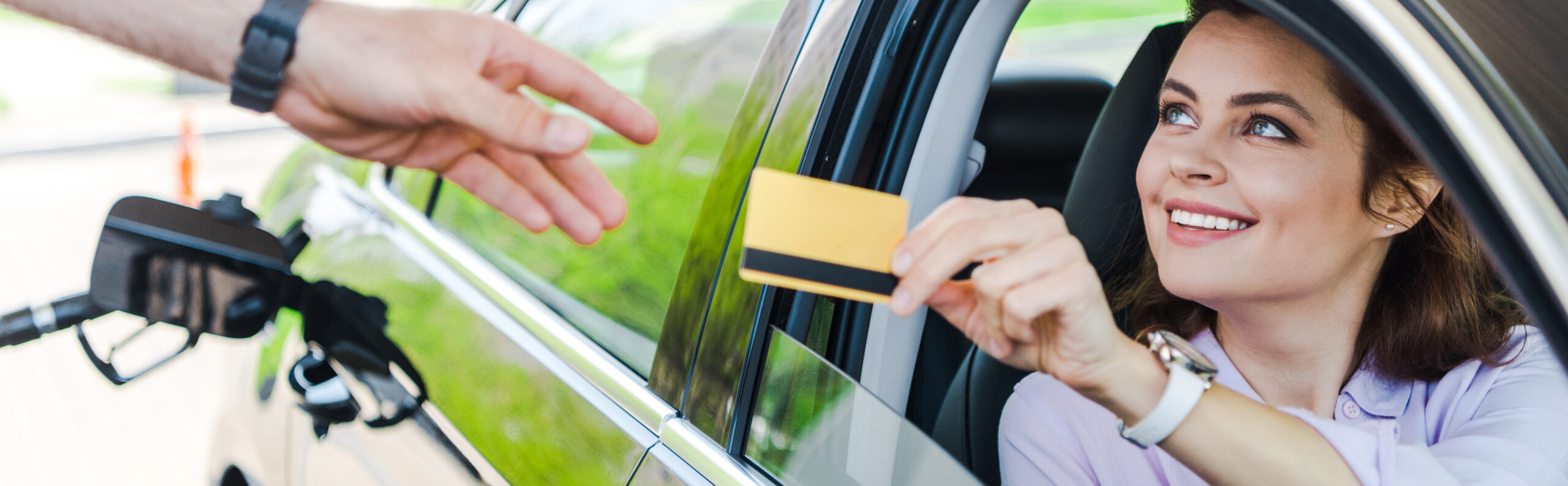 panoramic shot of cheerful woman sitting in car and giving credit card to worker at gas station